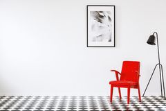 Red armchair next to black lamp on checkerboard floor in empty i. Nterior with poster and copy space. Place for your table stock images