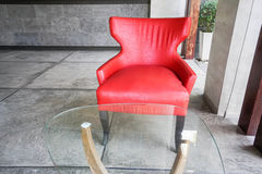 Red armchair and table with glass on top Royalty Free Stock Photography
