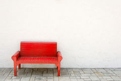 Red armchair a white wall and grey floor Stock Image