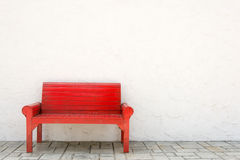 Red armchair a white wall and grey floor Royalty Free Stock Photography