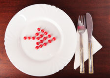 Red arrow from balls towards cutlery Stock Photography
