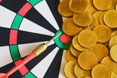 Red arrow dart board on Gold coin money for business success stock image