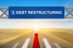 Red arrow and debt restructuring on blue road sign. With blurred background Royalty Free Stock Image