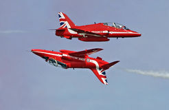 Red arrow inverted flyby. Photo of two red arrow jets performing an inverted flyby over the skies of herne bay in kent during summer air show of 2015 Stock Photo