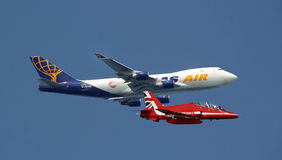 Red arrow jet and cargo plane. Photo of a red arrow jet flying past a cargo plane en-route to an air show in kent herne bay during summer of 2015 Royalty Free Stock Images