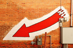 Red Arrow Painted on a Brick Wall Stock Photo