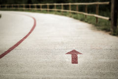 Red arrow painted on a pedestrian walkpath with a wooden fence Royalty Free Stock Photo