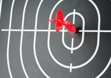 Red arrow shooting at center of black dart board Stock Photos