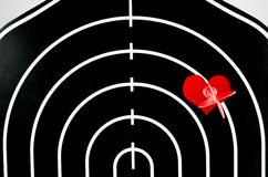 Red arrow shooting at heart position of profile shape black dart Stock Photo