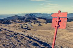 Red arrow and sign point guiding hikers. Velika Planina, Slovenia Stock Image