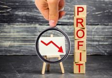 A red arrow to down and the inscription `profit`. Unsuccessful business and poverty. Profit decline. Loss of investment. Low wages. Economic crisis. The fall stock photography