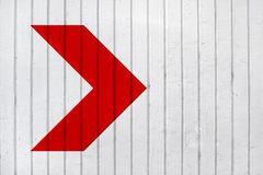 Red arrow on white wall Royalty Free Stock Photos