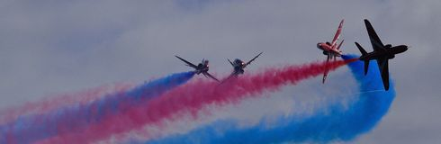 Red Arrows - Close up with Colourful smoke trails. Red Arrows - Close cross over formation flying Royalty Free Stock Images