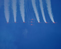 Red Arrows display. Red Arrows diving out of a loop Stock Photo