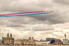RED ARROWS FLY OVER LIVERPOOL. Raf red arrow display team flying over liverpool and the river mersey supporting armed forces day in formation Royalty Free Stock Photos