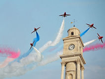 Red arrows over clock tower Royalty Free Stock Image