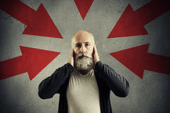 Red arrows pointing at serious man covering his ears Stock Photography