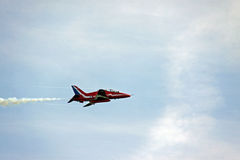A Red Arrows RAF Airforce jet aeroplane. A Red Arrows RAF Airforce aerobatic, formation flying jet aircraft in a blue sky with smoke trail royalty free stock photography