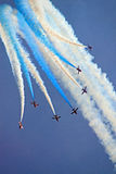 The Red Arrows RAF Airforce jet aeroplanes. The Red Arrows RAF Airforce aerobatic, formation flying jet aircraft in a blue sky with smoke trails Royalty Free Stock Images