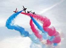 The Red Arrows RAF Airforce jet aeroplanes. The Red Arrows RAF Airforce aerobatic, formation flying jet aircraft in a blue sky with smoke trails Stock Images