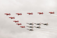 Red Arrows and Thunderbirds form up in a flypast. royalty free stock image