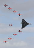 Red Arrows and Vulcan Bomber. A rare moment in time as the Red Arrows and Vulcan Bomber join together in flight Royalty Free Stock Photo