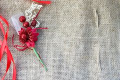 Red artificial flower with red festive ribbons on a background of brown old linen fabric texture, linen natural material with a co. Arse perpendicular Stock Image