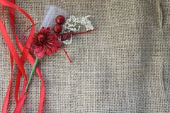 Red artificial flower with red festive ribbons on a background of brown old linen fabric texture, linen natural material with a co. Arse perpendicular Royalty Free Stock Image