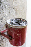Red ashtray on a wall full with cigarette old retro style not cleaned Royalty Free Stock Image