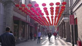 Red asian paper lanterns hanging over pedestrian shopping street, Beijing, China stock footage