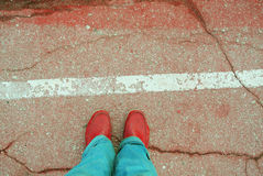 Red asphalt with line and legs in red shoes Royalty Free Stock Images