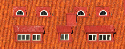 Red attic windows in orange tiled roof Stock Photo