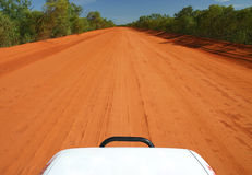 Red Australian road. Red Australian rural road with blue sky. Perspective from the car hood. Copy space Royalty Free Stock Photos