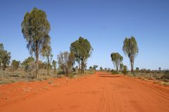 Red Australian rural road. Blue clear sky over the red Australian rural road. Rainbow valley, Southern Northern Territory, Australia Royalty Free Stock Images