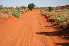 Red Australian shruby landcape. Red Australian rural road with shruby landcape. Rainbow valley, Southern Northern Territory, Australia Royalty Free Stock Photos