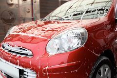 Red auto with foam at car wash royalty free stock photo