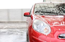 Red auto with foam at car wash. stock image