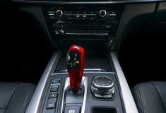 Red Automatic gear stick transmission of a modern car, multimedia and navigation control buttons. Car interior details. Transmission shift stock photography