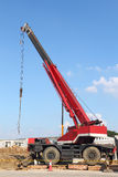 Red automobile crane against blue sky Royalty Free Stock Image
