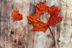 A red autumn sheet with heart on a wooden subsoil Royalty Free Stock Photography