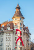 Red awareness ribbon on a Bucharest old building Royalty Free Stock Photo