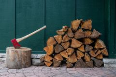 Red Axe and Pile of Fire Wood. In front of dark green wall Stock Photo