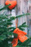 Red baby mittens hanging on the branches of spruce and a red plush heart in the background. Tinted photo royalty free stock images