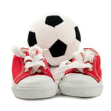 Red baby sneakers with a ball Royalty Free Stock Photography
