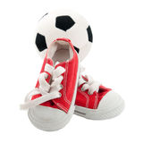 Red baby sneakers with a ball isolated on white Royalty Free Stock Photos