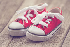 Red baby sneakers on wooden background. Vintage image Royalty Free Stock Images