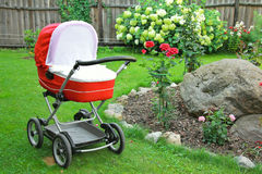 Red baby stroller on nature in park Stock Images
