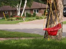 Red baby swing in suburban neighborhood Royalty Free Stock Photography