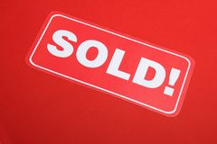 Card with text sold. On a red background a card with words sold Royalty Free Stock Photography