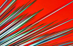 Red background. Colored strips diverge from the bottom to the  top. Abstract unique illustration and decoration. Green, white and blue colors on a red picture Stock Image